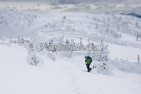 caucasian snowshoer walking up snowy hillside