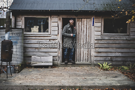 bearded man standing in doorway of