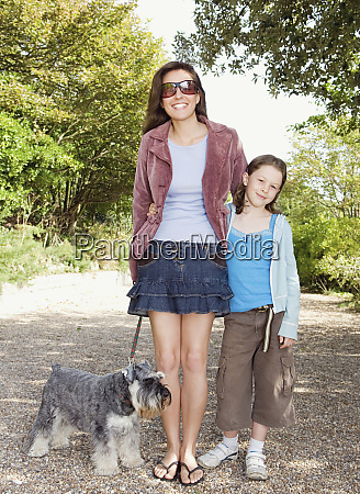 caucasian mother and daughter walking dog