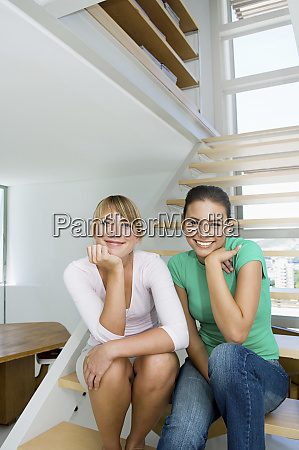 caucasian women sitting on staircase in