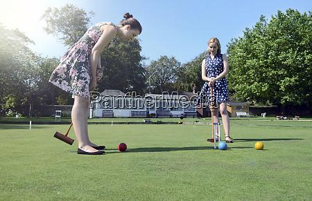 caucasian women playing croquet on lawn