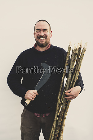 bearded man holding bill hook and