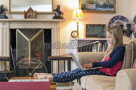 caucasian girl sitting on sofa using