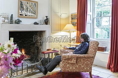 caucasian man sitting in armchair near