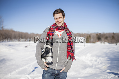 caucasian man carrying ice skates in