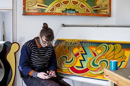kuenstlerin die an einer zeichnung sitzt