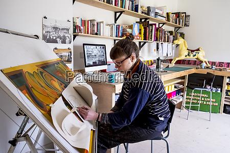 kuenstlerin sitzt an einem gekippten zeichentisch