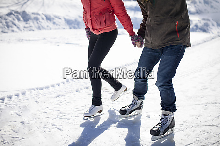 caucasian couple ice skating on snowy