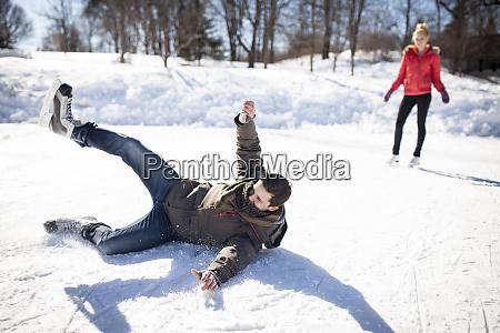 caucasian man falling while ice skating