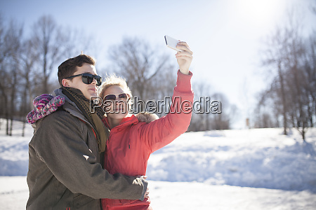 caucasian couple taking cell phone selfie