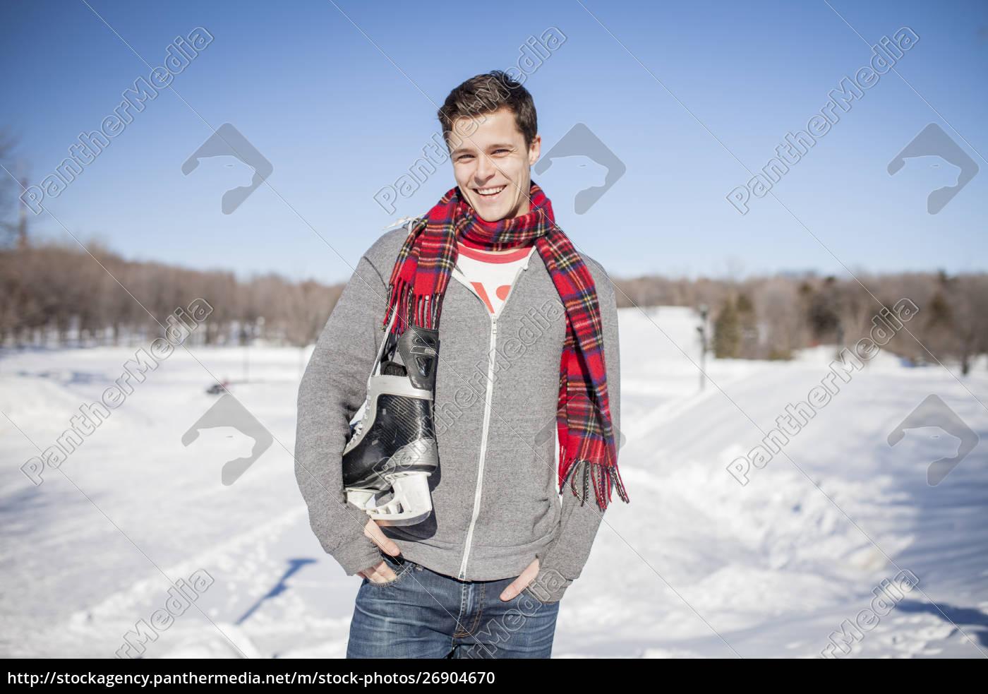 caucasian, man, carrying, ice, skates, in - 26904670