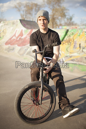 caucasian man riding bmx bicycle at