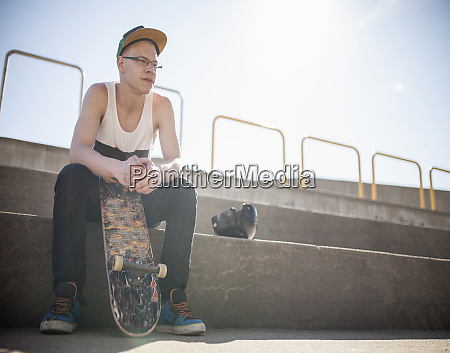 caucasian man with skateboard sitting on