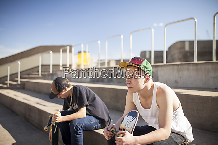 caucasian men with skateboards sitting on