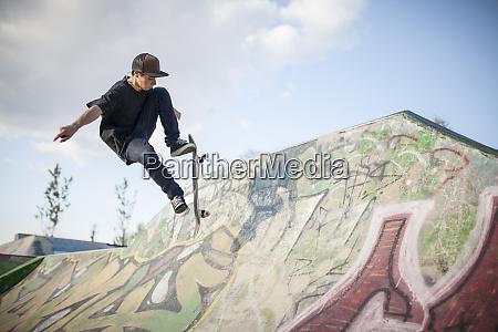 kaukasischer mann beim skaten im skatepark