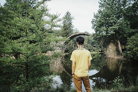 teenage boy looking at tranquil rakotzbruecke
