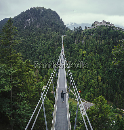 people walking across suspension bridge over