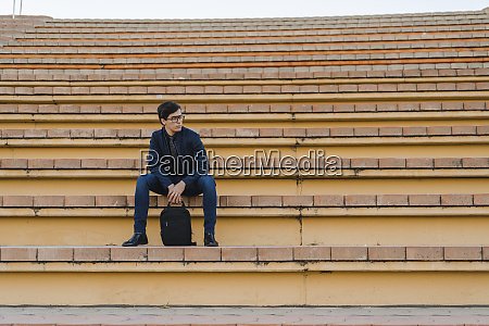 young businessman with backpack sitting on