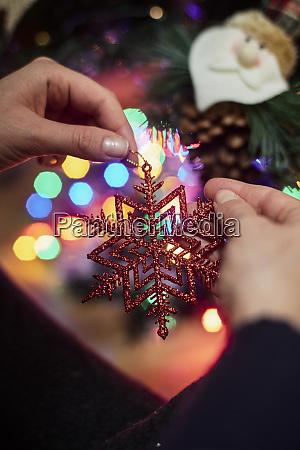 die hand der frau die weihnachtsschmuck
