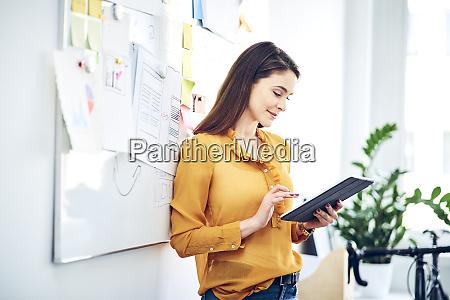 laechelnde geschaeftsfrau mit tablet am whiteboard