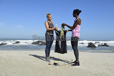 zwei frauen reinigen den strand aus
