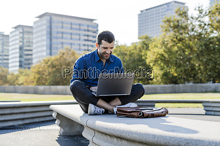 smiling businessman sitting on bench outdoors