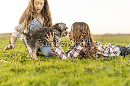 two girls playing with dog on