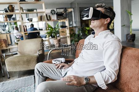 mature man wearing vr glasses sitting