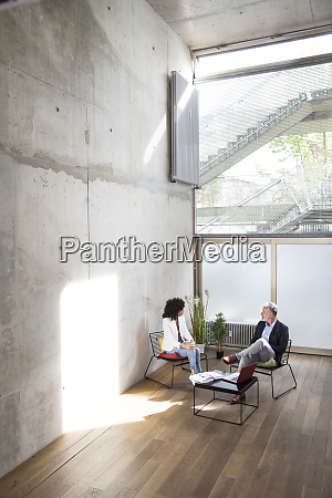businessman and businesswoman sitting in a