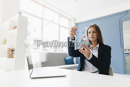 female scientist studying molecule model