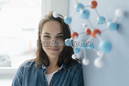 female scientist studying molecule model looking