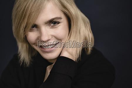 portraet einer laechelnden blonden jungen frau