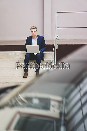 young businessman with skateboard sitting outdoors