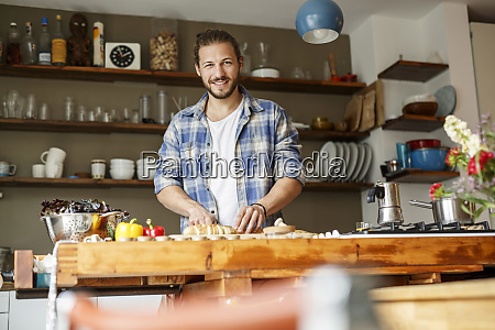 young man preparing food at home