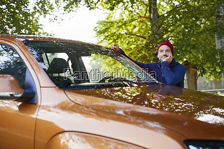 mature man leaning on car in