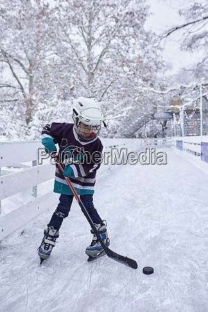 junge spielt eishockey auf der eisbahn
