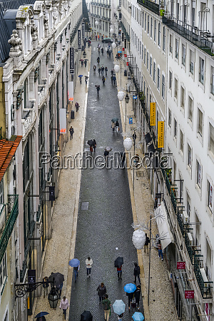 pedestrians with umbrellas walk the narrow