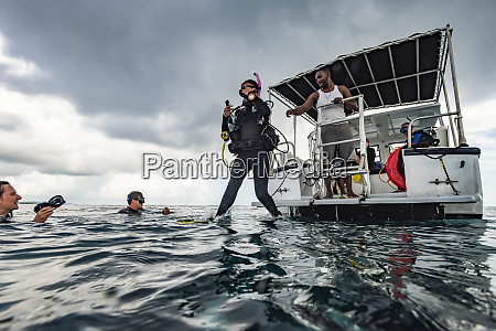 scuba divers enter the water from