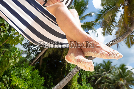 sand on womans feet sitting on