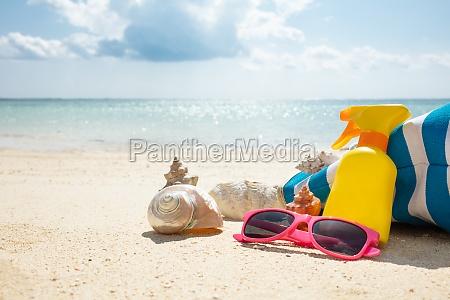sunglasses seashells and handbag on beach