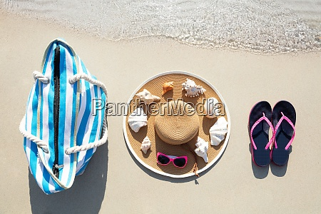female accessories on the sand at