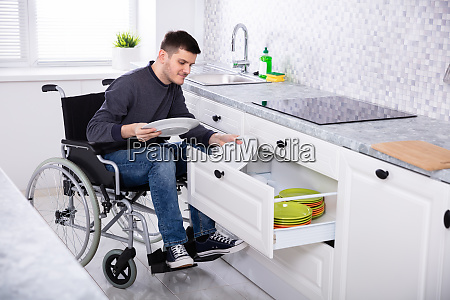 disabled man sitting on wheelchair arranging