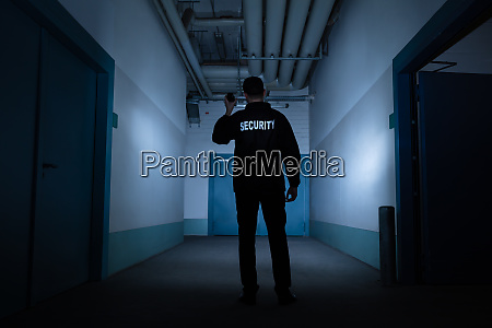 male security guard standing in corridor