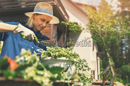 happy young woman planting summer flowers