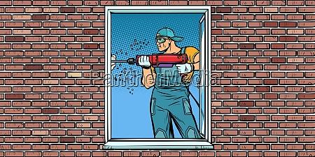 ein arbeiter installiert ein fenster bohrt