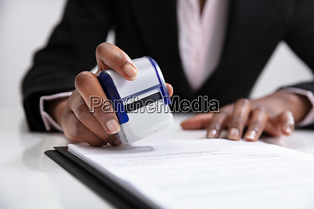 businesswoman putting stamp on documents