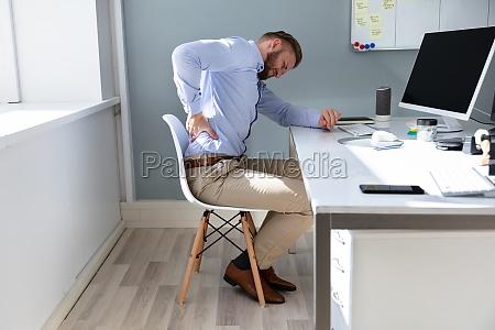 geschaeftsmann mit rueckenschmerzen