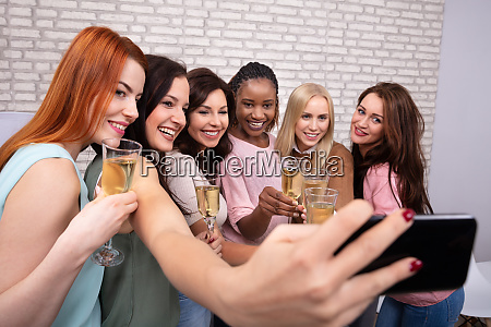 women with champagne taking selfie at