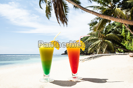 colorful cocktail glasses on the sandy