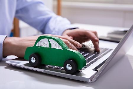 gruenes auto auf laptop tastatur